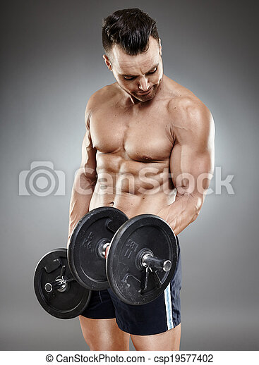 Athletic man working out with dumbbells - csp19577402