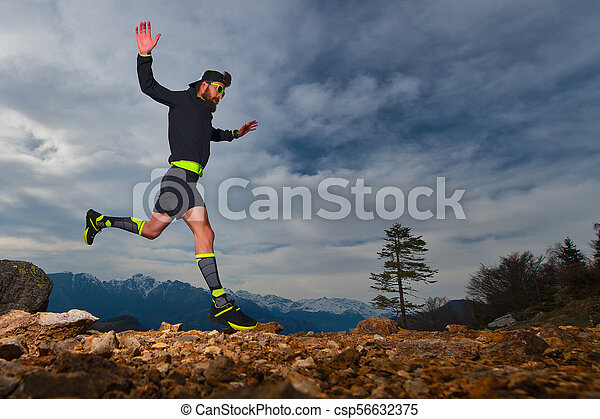 Athletic preparation of a man for trail running competitions in the mountains - csp56632375