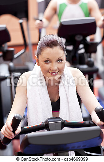 Athletic woman using a bicycle in a sport centre - csp4669099
