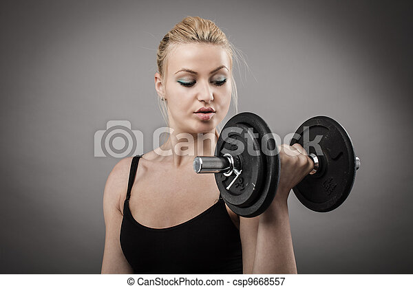 Athletic young lady working out with weights - csp9668557