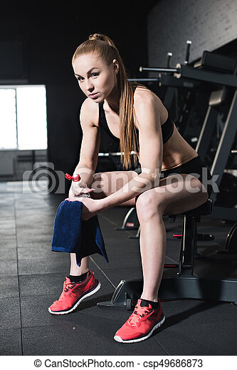 Athletic young woman in sportswear holding towel and bottle of water in gym - csp49686873