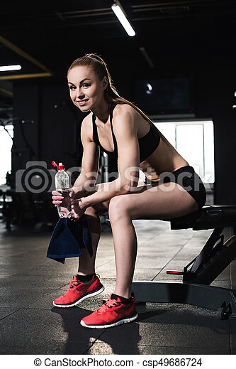 Athletic young woman in sportswear holding towel and bottle of water in gym - csp49686724