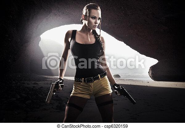 Una joven atlética con pistola - csp6320159