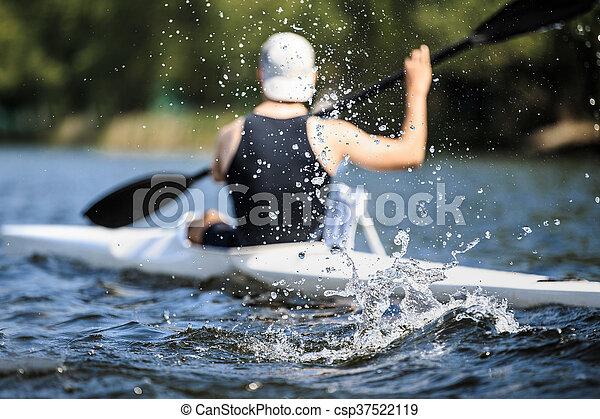 Atleta remando kayak en el lago durante la competencia - csp37522119