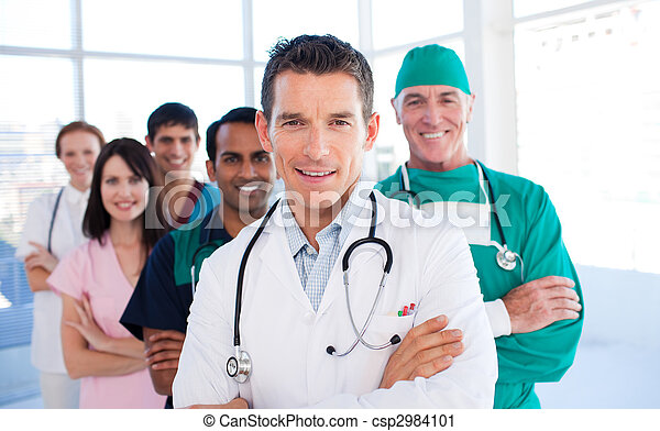 Atractive doctor standing with his colleagues  - csp2984101