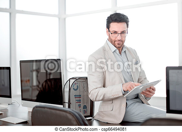 attentive businessman uses a digital tablet in a modern office. - csp66494081