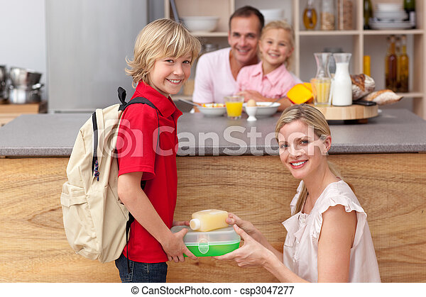 Attentive mother packing the school lunch to his son  - csp3047277