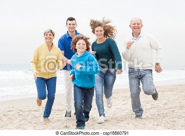 Una familia feliz corriendo en la playa - csp18860791