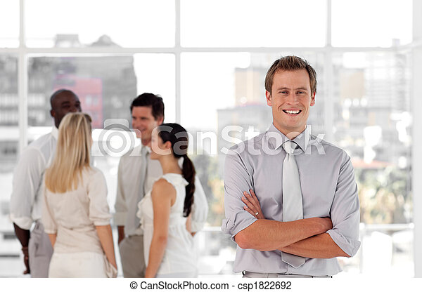 Attracive and confident business man in front of a group of associates smiling - csp1822692