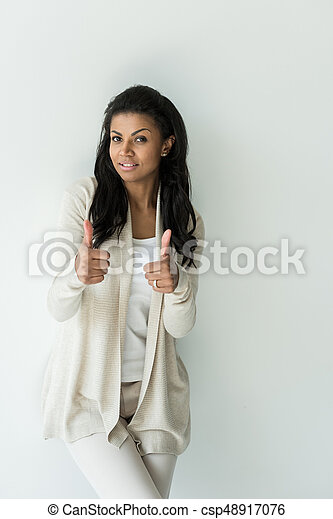 attractive african american woman showing thumbs up on white - csp48917076