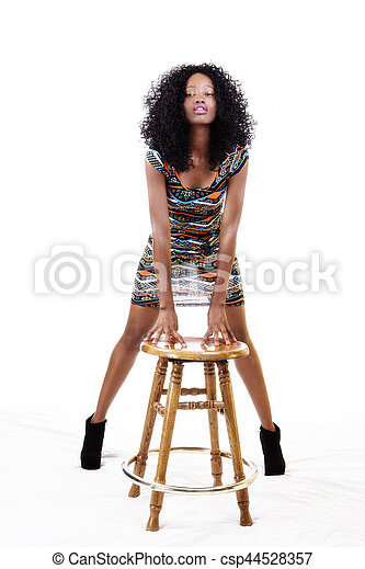 Attractive African American Woman Standing Hands On Stool - csp44528357