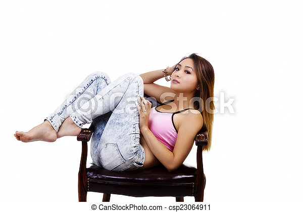 Attractive Asian American Woman Sitting In Chair - csp23064911