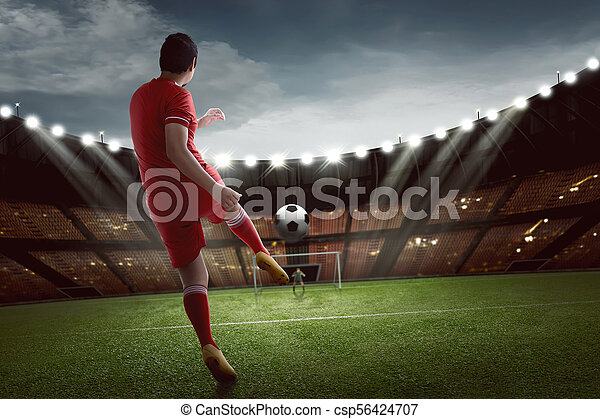 Attractive asian football player shooting the ball to goal - csp56424707