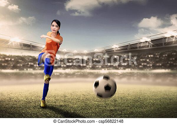 Attractive asian footballer woman kicking ball during match - csp56822148