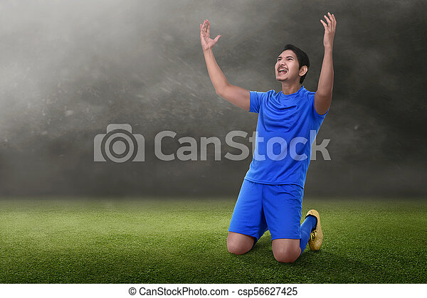 Attractive asian soccer player celebrate his victory - csp56627425