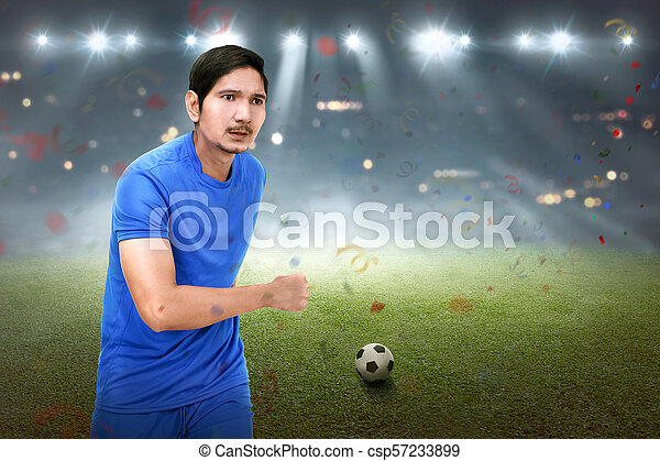 Attractive asian soccer player man running with ball - csp57233899