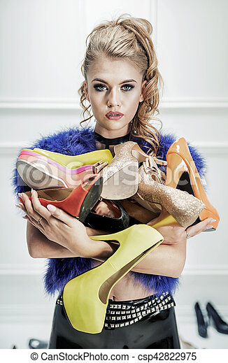 Attractive blond lady holding a bunch of shoes - csp42822975