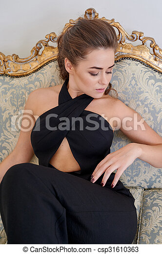 attractive blond woman in black dress sitting on the couch - csp31610363