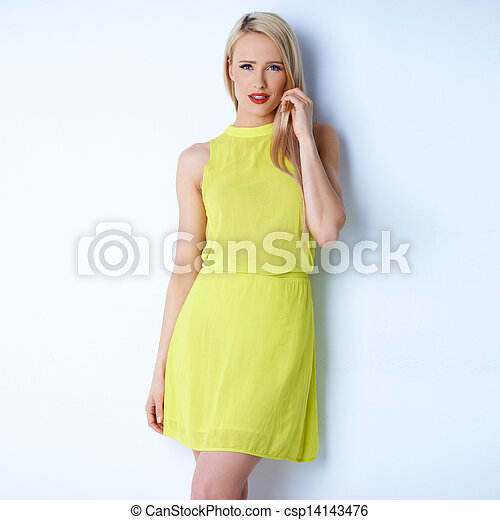 Attractive blond young woman posing in yellow dress - csp14143476