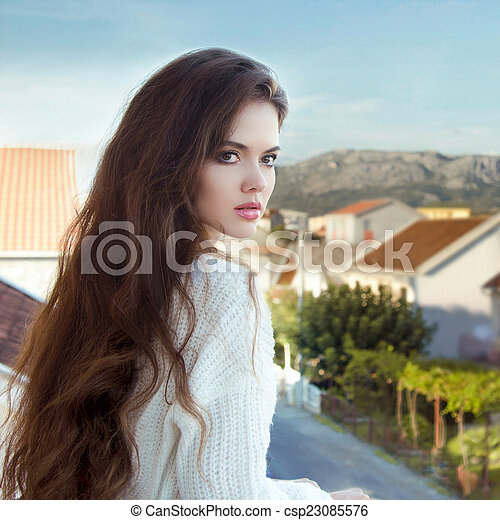 Attractive brunette Girl With Healthy Long Wavy Hair standing on - csp23085576