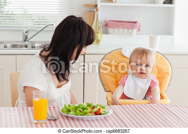 Attractive brunette woman having a meal with her baby while sitting in the kitchen - csp6683267
