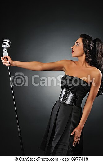 Attractive brunette woman with a retro microphone - csp10977418