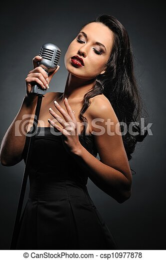 Attractive brunette woman with a retro microphone   - csp10977878