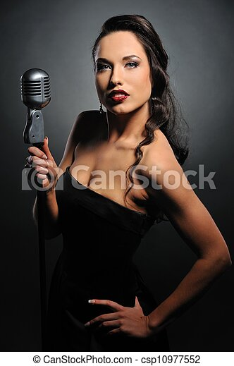 Attractive brunette woman with a retro microphone   - csp10977552