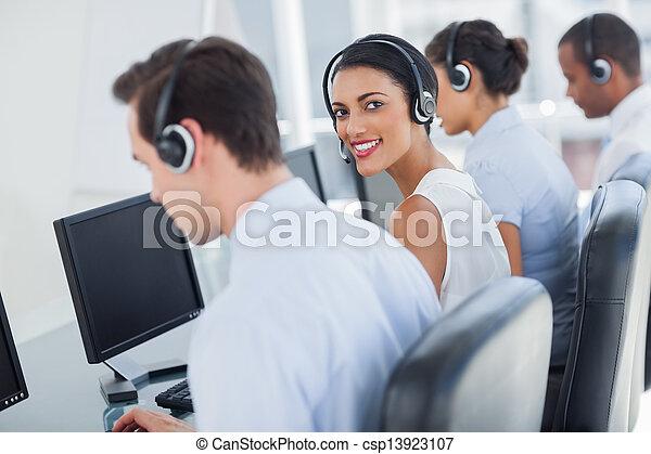 Attractive call centre employee looking over shoulder - csp13923107
