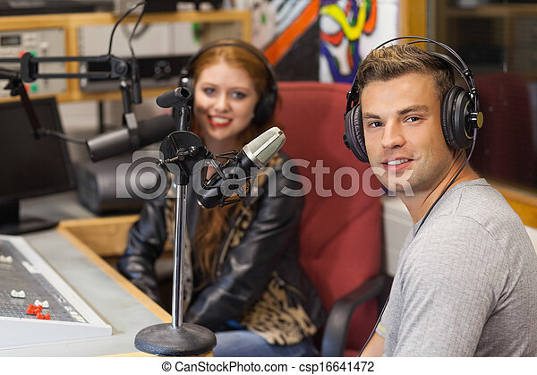 Attractive cheerful radio host interviewing a guest - csp16641472