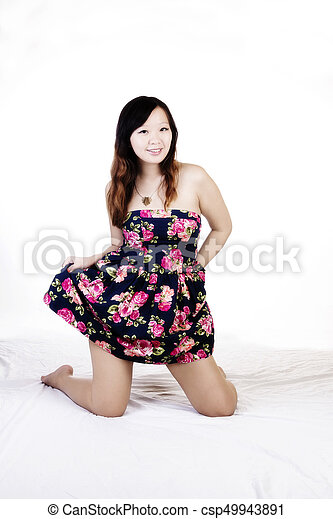 Attractive Chinese American Woman On Knees In Floral Dress - csp49943891