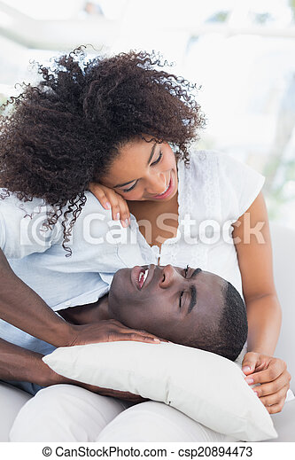 Attractive couple cuddling on the couch - csp20894473