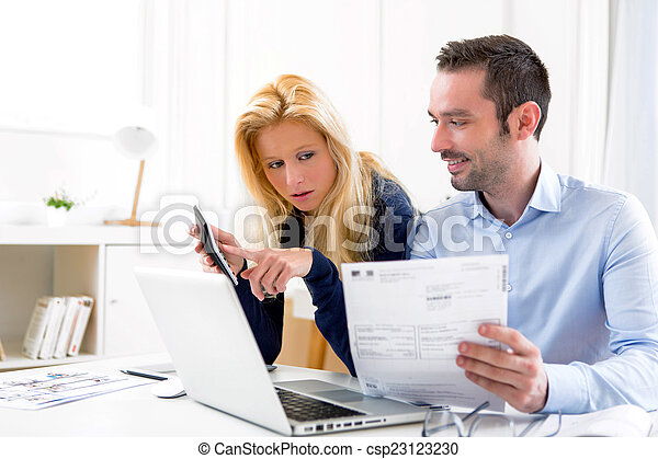 Attractive couple doing administrative paperwork - csp23123230