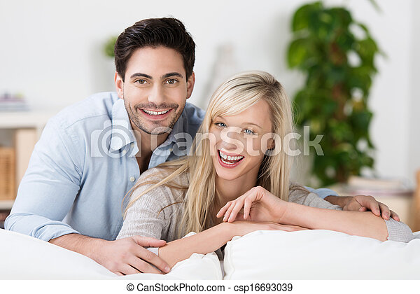 Attractive couple laughing at home - csp16693039
