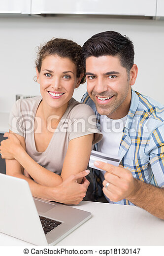 Attractive couple using laptop together to shop online - csp18130147