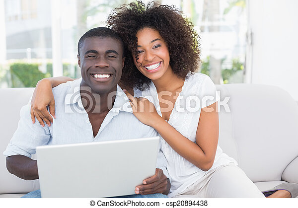 Attractive couple using laptop together on sofa - csp20894438