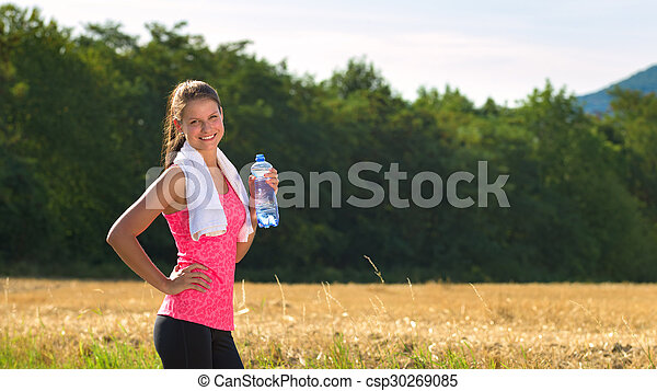 Attractive female taking a break after jogging, holding bottle of water - csp30269085