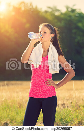 Attractive female taking a break after jogging, holding bottle of water - csp30269067