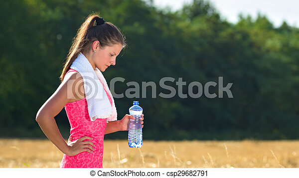 Attractive female taking a break after jogging, holding bottle of water - csp29682791