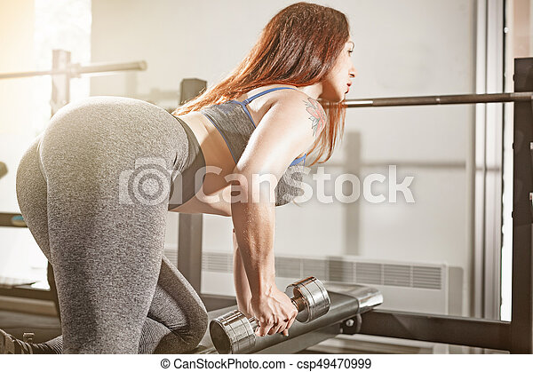 Attractive fit woman works out with dumbbells as a fitness conceptual over gym background.