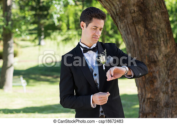 Attractive groom checking time in garden - csp18672483