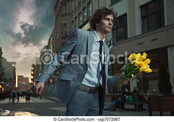 Attractive guy with bunch of tulips - csp7072987