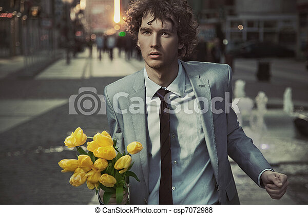Attractive guy with bunch of tulips - csp7072988