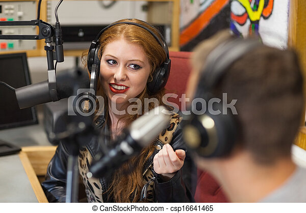 Attractive happy radio host interviewing a guest - csp16641465