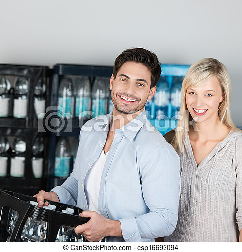 Attractive healthy couple buying bottled water - csp16693094