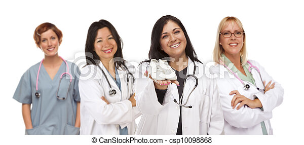 Attractive Hispanic Female Doctor or Nurse Holding Out Baby Shoes and Support Staff Behind Isolated on a White Background. - csp10098868