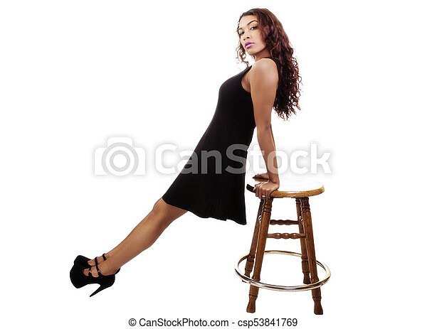 Attractive Hispanic Lady In Black Dress Leaning On Stool - csp53841769