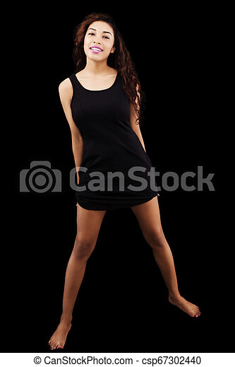 Attractive Hispanic Woman In Black Dress On Dark Background - csp67302440