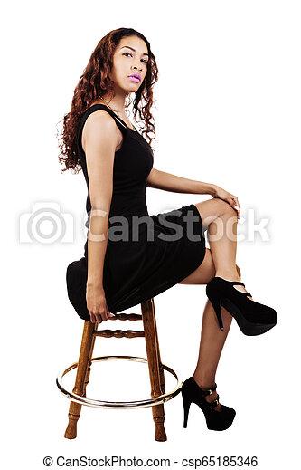 Attractive Hispanic Woman Sitting In Black Dress On Wooden Stool - csp65185346