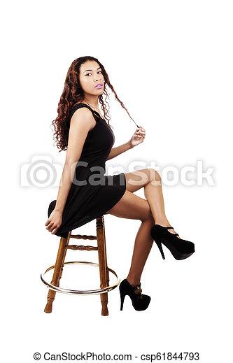 Attractive Hispanic Woman Sitting In Black Dress On Stool - csp61844793